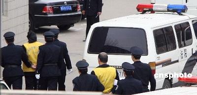 图为耿金平等犯罪嫌疑人被从后门押送进入法院。中新社发 翟羽佳 摄
