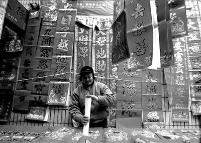 四川安县安昌镇的一家春联摊前,挂满了喜庆的春联。