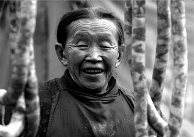 春节将至,映秀镇上的王婆婆站在自家的腊肠年货后笑容满面。