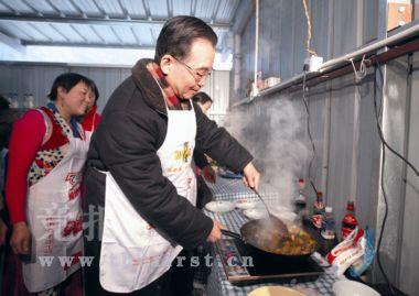 温家宝总理来到四川受灾最为严重的北川、德阳、汶川等地。1月25日,总理在汶川映秀镇板房安置小区吴志远家吃年夜饭时,请大家品尝他刚炒出的回锅肉。 新华社/供图