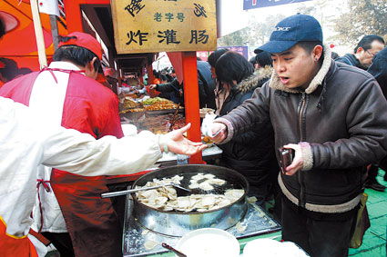 """徐德亮挑了一个人少的摊子买了一盘灌肠。吃了一口后,亮子悻悻地说:""""怪不得这家没人排队呢。"""" 图/杨威"""