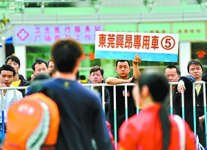 昨天,一位来自东莞某工厂的职员举着接人专车的牌子在火车站出站口等待刚刚到达广州的务工人员。 记者乔军伟摄