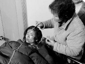 多数伤者手、足、头部被严重烧伤,一名家属在细心照料伤者。