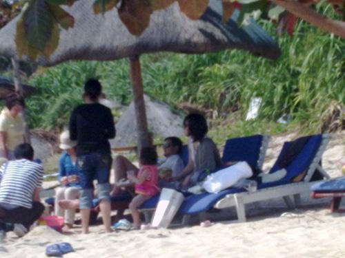 图中显示,李亚鹏与王菲、李嫣在遮阳伞下休息