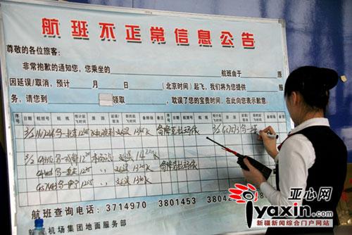 为了让旅客了解航班情况,工作人员将延误的航班都写在提示板上。亚心网记者 李远新 摄