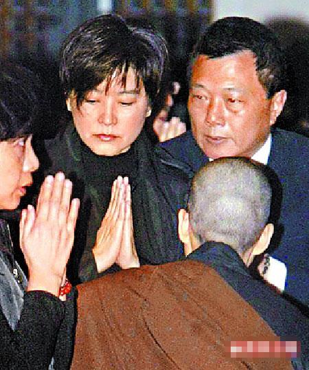 林青霞(中)在法鼓山上双手合十默祷,师姐在前引导她参拜圣严法师法相