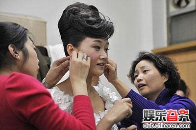 工作人员在帮宋祖英换耳环,两个耳朵两个人侍候