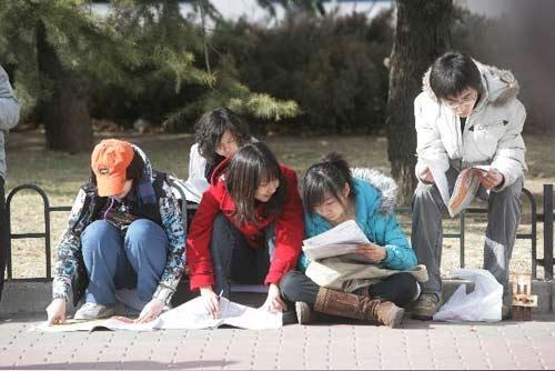 在场外看信息的求职学生们