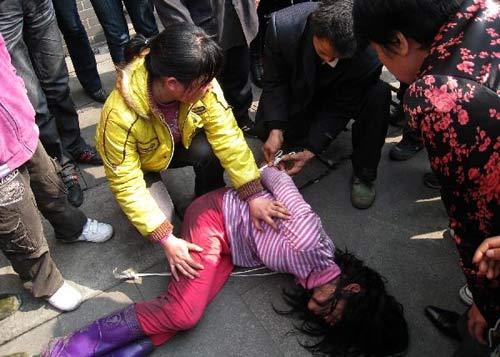 青年男女将少女压倒在地后,男的用尼龙绳在捆绑少女的双手。