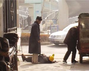 老汉躺在冰冷的大街上。截屏照片