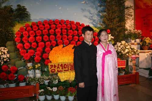 """2月14日,一对朝鲜青年在首都平壤举行的第13届""""金正日花""""展览会上合影。新华社记者高浩荣摄"""