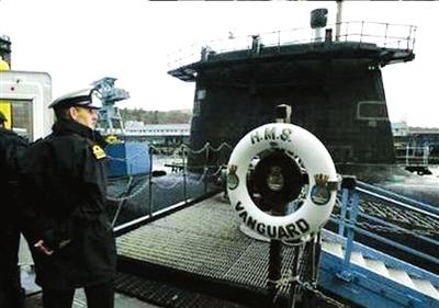 """在格拉斯哥附近英国海军基地,一名英国海军官员站在英国""""前卫""""号核潜艇前。资料图片"""
