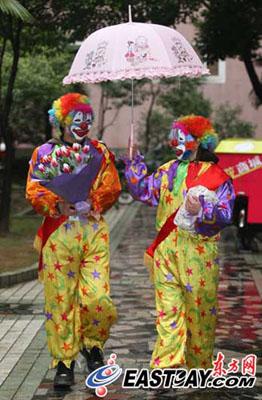 带上客户的鲜花和礼物,两名小丑快递员撑起卡通雨伞,开始工作。 东方网记者刘歆 摄