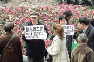 昨日,沙坪坝三峡广场,六旬老人余柏容、湛正芳举牌找工作,想找钱救儿子。本报记者 许恢毅 摄