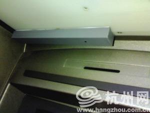 ATM机左上方有个灰色长条形盒子,上端有白色的胶水露在外面,盒子右边有个小孔。银行专家说,这是加装了摄像头的MP4。盒子上的小孔就是摄像头,正对着键盘,用来记录银行卡密码。