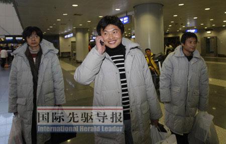 回家的感觉真好。图为2月25日,在首都国际机场,李广超(中)笑着给家人打电话报平安。本报记者 邢广利/摄