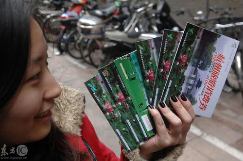 买到的群众开心地展示杭州旅游消费卷