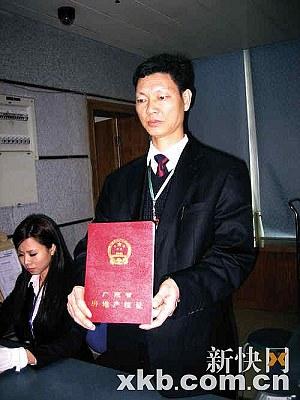 市房地产交易中心工作人员向市民展示新版房产证。