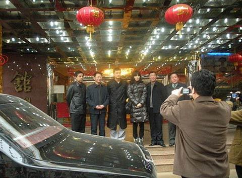 王菲李亚鹏与当地县长等一群人从宾馆出来。