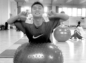 队员黄良财在球上努力保持平衡,他身后的队友已经掉到了地上