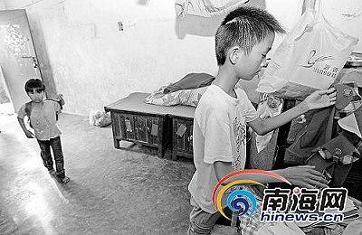 阿胜(右)在整理衣服,身后是放学回家的7岁妹妹爱利记者李小岗摄
