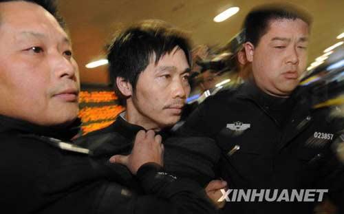 3月5日晚,在贵阳机场,杀害贵州省黔西县花溪乡7名村民的重要犯罪嫌疑人胡云超(中)被警方从浙江省慈溪市押回。新华社记者 杨楹 摄
