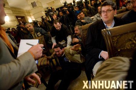 这张摄于2008年12月14日的资料照片显示伊拉克记者蒙塔兹·扎伊迪(中)在伊拉克首都巴格达举行的一场记者招待会上向美国总统布什扔鞋后被按倒在地。2009年3月12日,伊拉克一法院判处向美国前总统布什扔鞋抗议的伊拉克记者蒙塔兹·扎伊迪3年有期徒刑。新华社发