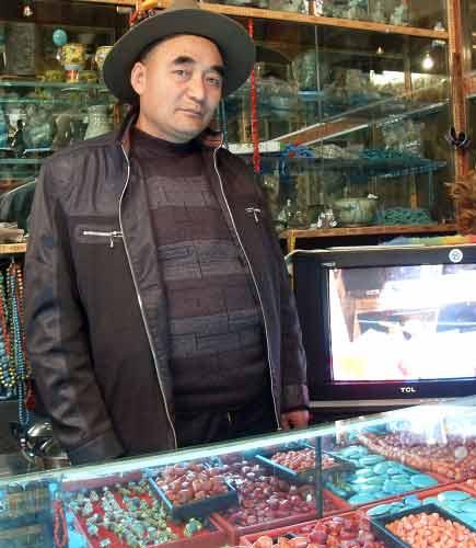 喜学义在自己的店铺内。电视上正在播放他的店去年遭破坏的录像。