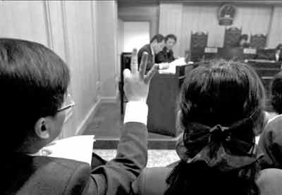 周成宇在庭审中不时用手势与代理律师交流,直至被法官制止。