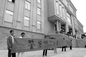 被告吉忠春的家人也在法庭外拉起横幅记者高峰/摄