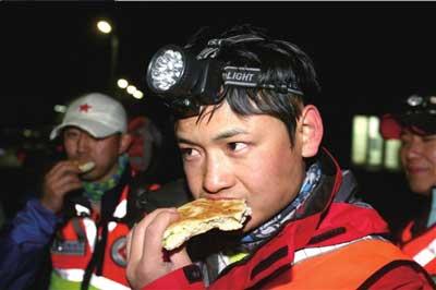 昨晚21时,饥肠辘辘的救援队员在吃晚餐。本版图片本报记者周民摄