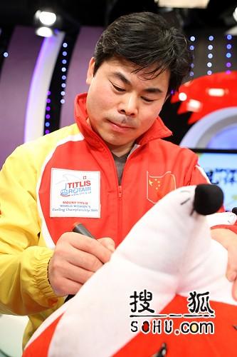 图文:女子冰壶队做客搜狐 谭伟东在狐狸上签名