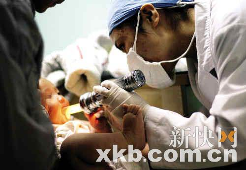 医生在为一名疑患有手足口病的儿童检查口腔。 新快报记者 李小萌/摄