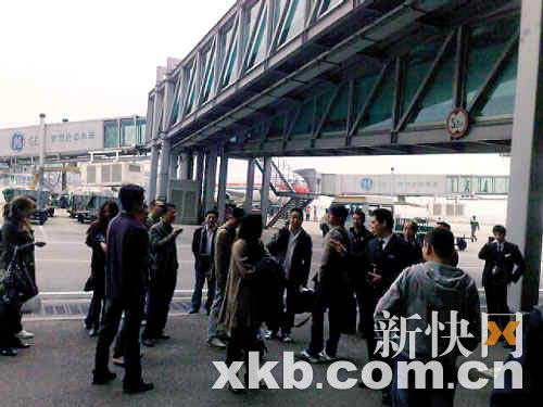 航班延误后部分旅客冲过登机口进入廊桥下。