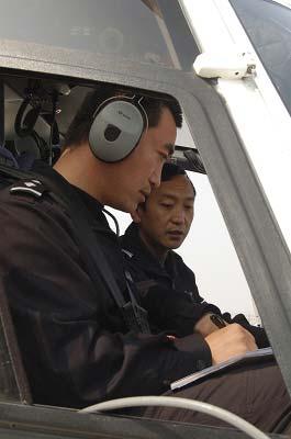 直升机上的民警空中监控地面交通。
