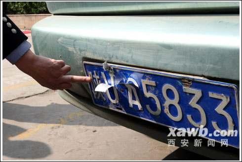 """作案前嫌犯给车牌上贴上即时贴,车号就变成了""""警用的""""。"""