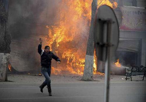 3.14事件中,一名妇女逃出燃烧的店铺并挥手求救。