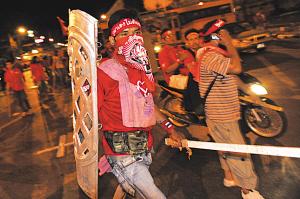 一名示威者手持盾牌和木棍走在曼谷总理府附近的街道上。