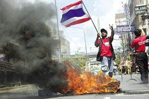 一名示威者在被燃烧的轮胎旁挥旗。