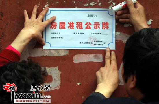"""4月14日,乌鲁木齐市和平路街道办事处黑甲山前街社区的工作人员在给辖区里的出租户张贴""""出租房屋公示牌""""。"""