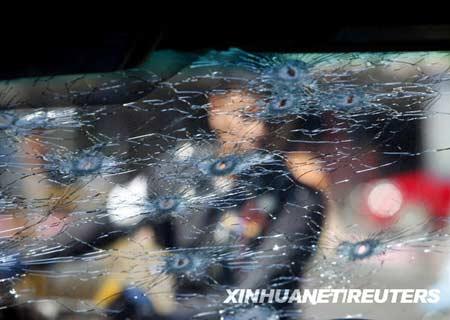 4月17日,在泰国首都曼谷,一名警察查看一辆遭袭的汽车。当日,泰国人民民主联盟(民盟)领导人颂提林通恭乘坐这辆汽车在曼谷遭枪击受伤。颂提已被送往医院接受治疗。新华社/路透