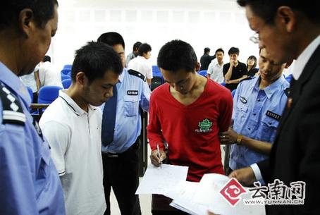 谢宏、陈光吕在判决书上签名 记者 王法 摄(一审宣判,资料图片)