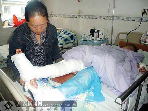 毛权的母亲正在照顾身负重伤的儿子。记者 邓振福摄