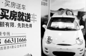"""4月17日,在苏州市体育中心举行的购房节活动中,一家参展企业推出""""买房送车""""让利措施吸引消费者。"""