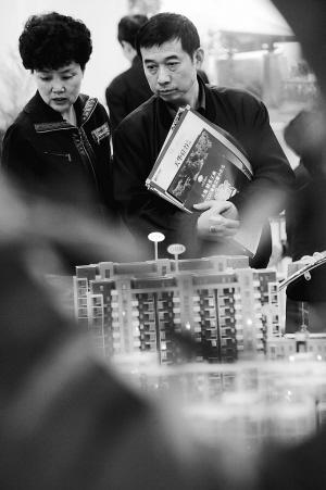 4月16日,2009年南京春季房地产商品交易会开幕。两位南京市民在楼盘模型前参观。