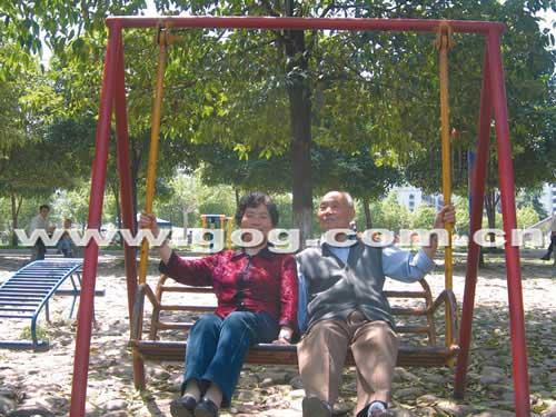 两位精神矍铄的老人相依坐在一起荡秋千,谈笑风生