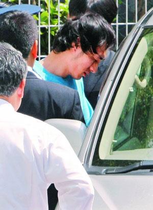 昨日下午,草剪刚(蓝衣者)被押上警车时垂头丧气