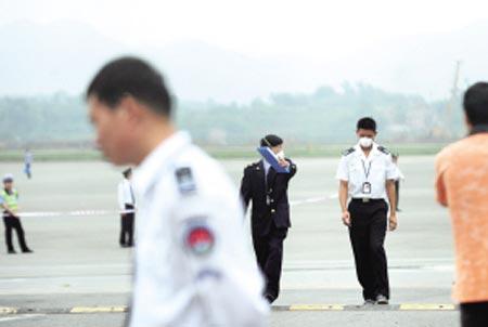 """演习中,一名""""疑似病人(白衣者)""""被带离停机坪。 记者 冉文 摄"""