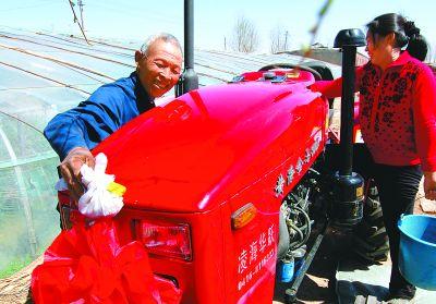 辽宁省锦州市大薛乡流水村六十三岁农民周广海(左)擦拭新买的享受补贴的拖拉机。李铁成摄