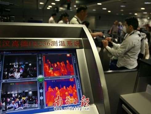 检验检疫局工作人员红外线体温探测仪为航班乘客做相关检查。吴伟洪 摄